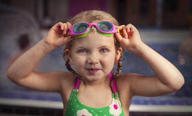 Small girl in pool with goggles