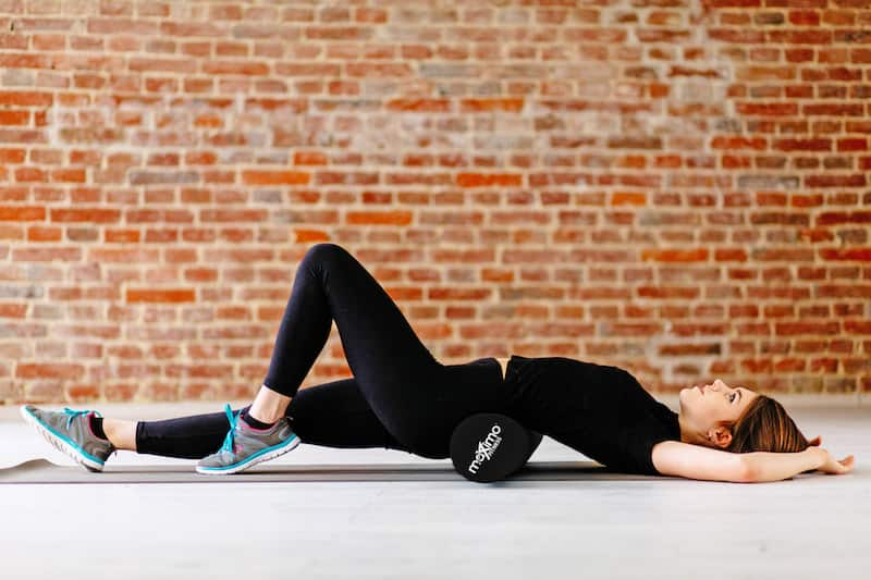 girl dressed in black using a foam roller