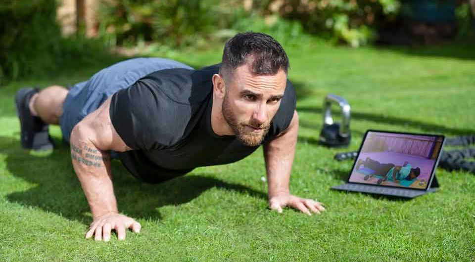 Man doing plank on green lawn